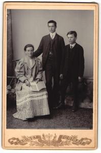 Fotografie Cabinet Portrait, unbekannter Ort, Portrait sitzende Dame und zwei junge Männer in hübscher Kleidung