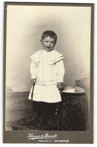 Fotografie Lissner & Brandt, Dresden-N, Portrait hübsch gekleidetes Mädchen mit Peitsche auf Stuhl stehend