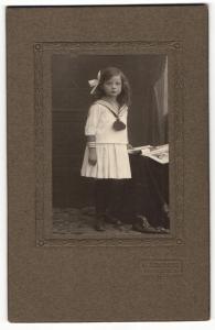 Fotografie A. Steinmetz, Neunkirchen, Portrait hübsch gekleidetes Mädchen mit Zeitung an Tisch gelehnt