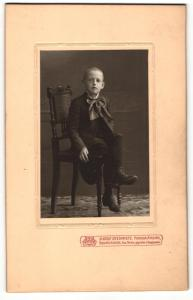 Fotografie Adolf Steinmetz, Neunkirchen Bez. Trier, kleiner auf einem Stuhl sitzender Junge im Anzug mit grosser Schleife