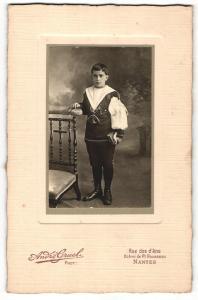 Fotografie Andre Gruel, Nantes, Portrait hübsch gekleideter Junge mit Buch an Stuhl gelehnt