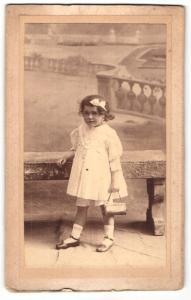 Fotografie William, Versailles, Portrait hübsch gekleidetes Mädchen mit Tasche an Bank gelehnt