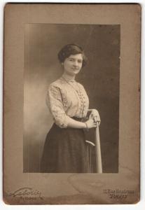 Fotografie Laborier, Paris, Portrait hübsch gekleidete Dame mit Armband an Stuhl gelehnt