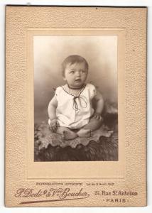 Fotografie P. Dode & Vve. Boucher, Paris, Portrait sitzendes Kleinkind im weissen Hemd mit kurzen Haaren