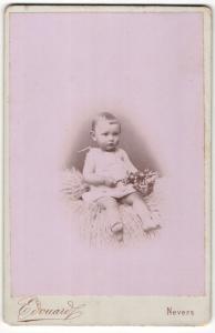 Fotografie Edouard, Nevers, Portrait sitzendes Kleinkind im Hemdchen mit Rassel