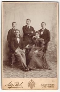Fotografie Aug. Red, Linz, Portrait drei Herren und sitzendes Paar in eleganter Kleidung