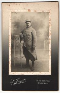 Fotografie L. Jayet, Orleans, Portrait Soldat im Uniformmantel an Tisch gelehnt
