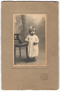 Fotografie Sarrazin, Poissy, Portrait hübsch gekleidetes kleines Mädchen an Stuhl gelehnt