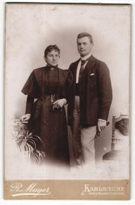 Fotografie R. Mayer, Karlsruhe, Portrait elegant gekleidetes Paar mit Buch an Tisch gelehnt