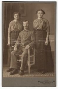 Fotografie Hans Schneider, Coburg, Portrait sitzender Soldat in Uniform und zwei bürgerliche Damen
