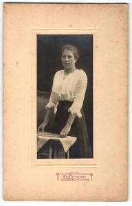 Fotografie Ed. Dickopf, Siegburg, Portrait modisch gekleidete Dame mit Karten an Tisch gelehnt