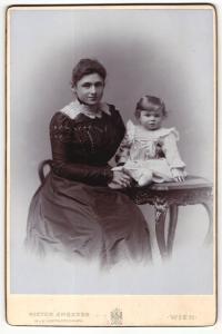 Fotografie Victor Angerer, Wien, Portrait junge Dame im hübschen Kleid mit Kleinkind am Tisch sitzend