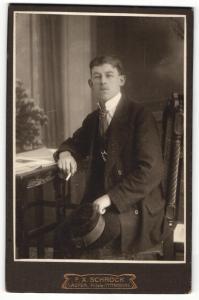 Fotografie F. X. Schröck, Laufen a / d. Salzach, Portrait elegant gekleideter Herr mit Zigarette am Tisch sitzend