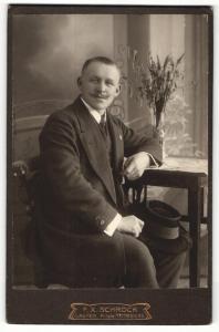 Fotografie F. X. Schröck, Laufen a / d. Salzach, Portrait elegant gekleideter Herrr mit Schnauzbart am Tisch sitzend