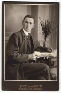 Fotografie F. X. Schröck, Laufen a / d. Salzach, Portrait elegant gekleideter Herr mit Zeitung am Tisch sitzend
