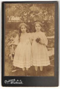 Fotografie Cabinet Portrait, unbekannter Ort, Portrait zwei kleine Mädchen in weissen Kleidern mit Blumen