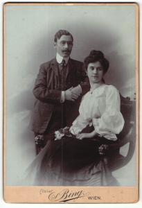 Fotografie Sigmund Bing, Wien, Portrait bürgerliches Paar in eleganter Kleidung mit Blume