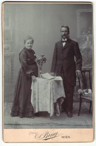 Fotografie Sigmund Bing, Wien, Portrait bürgerlich gekleidetes Paar mit Buch an Tisch gelehnt
