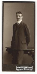 Fotografie W. Höffert Nachf., Hannover, Portrait elegant gekleideter Herr mit Schnauzbart an Tisch gelehnt