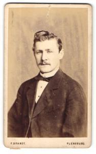 Fotografie F. Brandt, Flensburg, Portrait charmant blickender Mann mit Fliege im Jackett