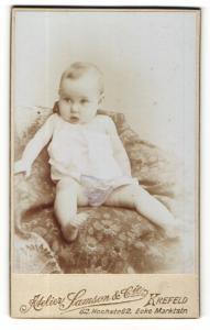 Fotografie Samson & Cie, Krefeld, Portrait bezauberndes Kleinkind im weissen Hemdchen