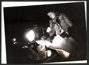 Fotografie Keystone, Ansicht London, 6. England Sternfahrt, Miss. D. Patten studiert Landkarte im Auto-Scheinwerferlicht