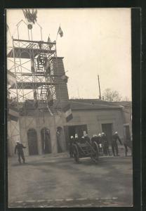 Foto-AK Feuerwehrleute in Uniform vor einem Gerüst