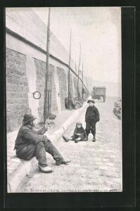 AK Paris, Berges de la Seine, Les habitues des berges et des ponts, Mann und Kinder sitzen auf der Strasse