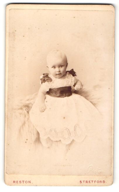 Fotografie Reston, Stretford, Baby in weissem Kleid auf Fell sitzend 0