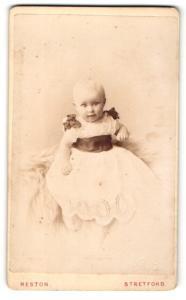 Fotografie Reston, Stretford, Baby in weissem Kleid auf Fell sitzend