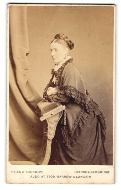 Fotografie Hills & Saunders, Oxford, Frau im Kleid auf Stuhllehne gestützt 0