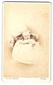 Fotografie Arthur Reston, Stretford, Baby im Kleidchen liegend