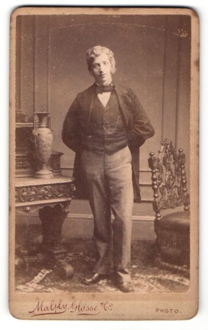 Fotografie Magly Glasse, Islington, Mann im Anzug stehend mit Fliege und den Armen hinter dem Rücken 0