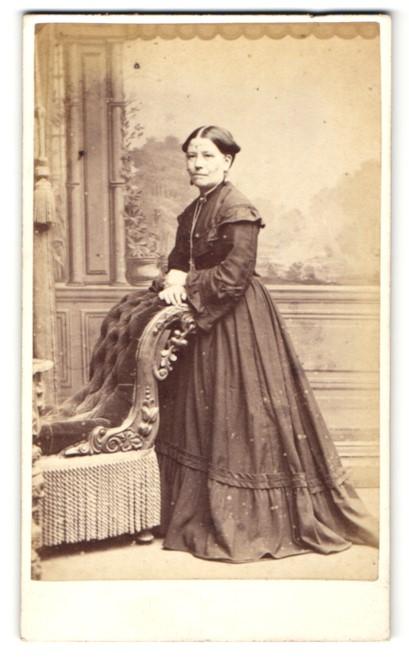 Fotografie W. H. Moore, Bristol, Frau im Kleid stehend mit den Händen auf Sessellehne abgelegt 0