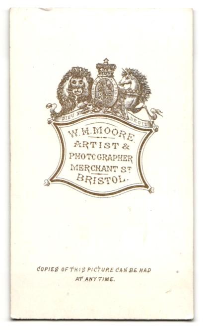 Fotografie W. H. Moore, Bristol, Frau im Kleid stehend mit den Händen auf Sessellehne abgelegt 1
