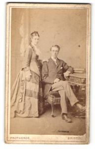 Fotografie Protheroe, Bristol, Mädchen im Kleid stehend neben jungen Mann im Anzug sitzend auf Stuhl