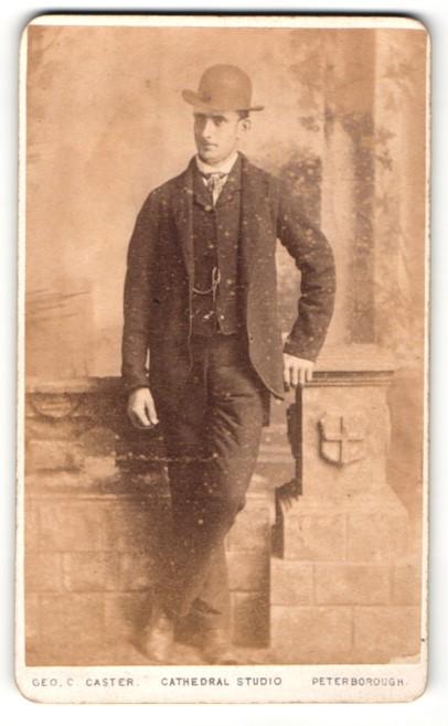 Fotografie Geo. C. Caster, Peterborough, Mann stehend im Anzug mit Hut und an Pfeiler gestützt 0
