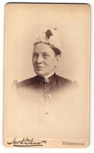 Fotografie E. Tham, Huddersfield, Dame mit Brosche am Kragen und Haube auf dem Kopf