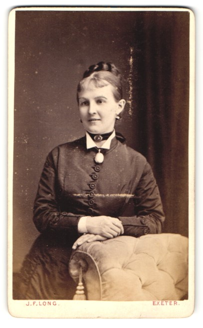 Fotografie J. F. Long, Exeter, Frau im Kleid mit Halsband und Brosche daran und Dutt 0