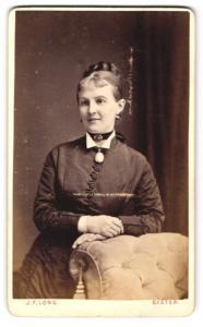 Fotografie J. F. Long, Exeter, Frau im Kleid mit Halsband und Brosche daran und Dutt