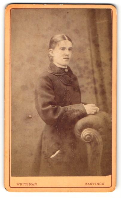 Fotografie Whiteman, Hastings, Mädchen im Mantel hinter Sessel stehend 0