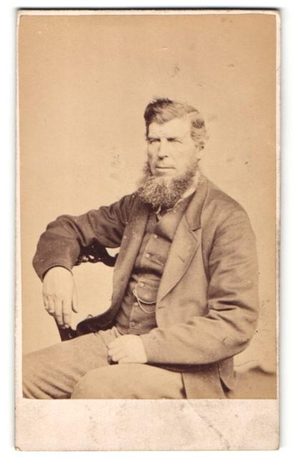 Fotografie J. Ballantine, Cumnock, Mann im Anzug sitzend mit krausem Vollbart 0