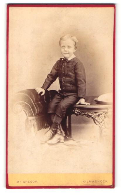 Fotografie Mc Gregor, Kilmarnock, Junge im Anzug mit Schleife am Hals auf Tisch sitzend 0