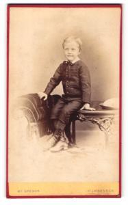 Fotografie Mc Gregor, Kilmarnock, Junge im Anzug mit Schleife am Hals auf Tisch sitzend