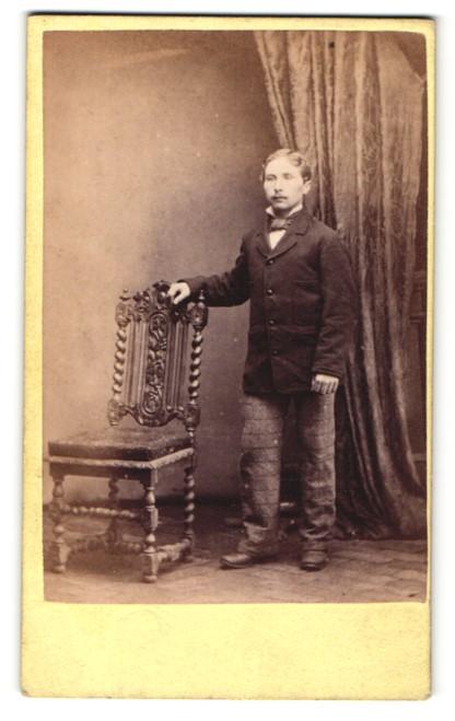 Fotografie Andrew Hodge, Stirling, kleiner Mann im Anzug stehend mit Arm auf Stuhllehne gestützt 0