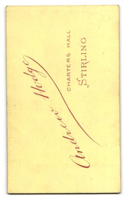 Fotografie Andrew Hodge, Stirling, kleiner Mann im Anzug stehend mit Arm auf Stuhllehne gestützt 1