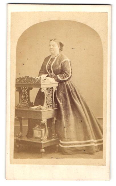 Fotografie Hills & Saunders, Eton, Frau im langen Kleid steht am Schreibschrank 0