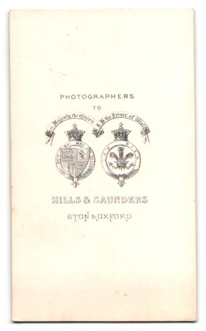 Fotografie Hills & Saunders, Eton, Frau im langen Kleid steht am Schreibschrank 1