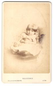 Fotografie Hills & Saunders, Eton, Portrait Kleinkind im Kleidchen auf einem Sessel