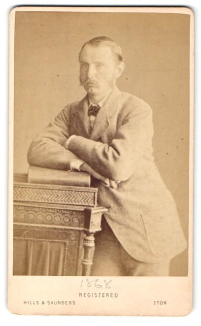 Fotografie Hills & Saunders, Eton, Portrait eleganter Herr im Anzug auf ein Buch gelehnt 0